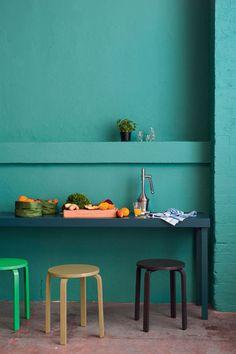 Cuisine avec un mur couleur océan et petits tabourets design
