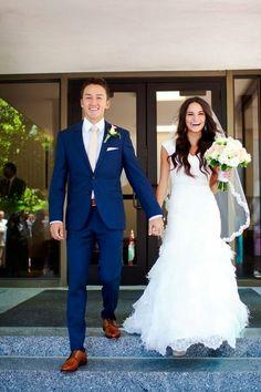 look de marié, costume bleu roi, chaussures en couleur caramel, assorties à la couleur de la ceinture, boutonnière ornée d'une fleur blanche, cravate en couleur ivoire