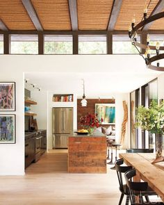 The kitchen island and shelving are made of reclaimed pine, the refrigerator and range are by Jenn-Air, and the wood sculpture is from Bali.