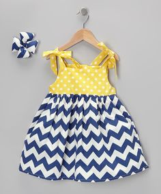 Decorated with darling chevrons and polka dots, this dreamy duo fashions a sublime sunny day look for any little sweetie. The classically-colored dress features charming tie-straps, while the complementary bow acts as a fetching accent up top.