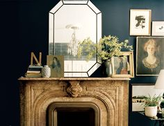 Add personality to a dark and glamorous room with a large mirror framed by flowers and a stack of colorful books.