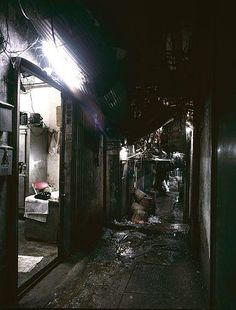 An alley in Kowloon Walled City. Before Hong Kong government organized regular garbage collection the triad let junkies carry out the piled up trash. Picture by Ian Lambot