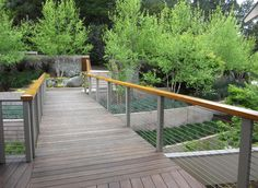 Wrought aluminum posts ground and pace the railing design. Metal wire helps to disappear the structure keeping the focus on the strong lines. Like the use of wood handrail for warmth. Great design!