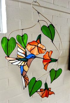 Stained glass suncatcher, glass hanger of bird, Hummingbird, Tiffany, window hanger, window art with different colors I make all different types of these wired hangers, please contact me for your special choice of bird or branche This one is about 40 cm in height If you order a different color, or the color of the picture, glass may vary from the original shown, even when same colors are used. Each sheet of glass is unique, and that's exactly how we love it, right?! I strive to make unique…