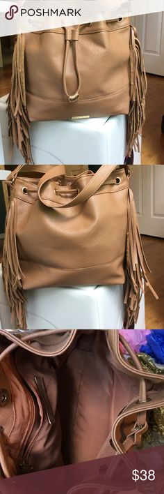 """TAN RAMPAGE LARGE DRAWSTRING FRINGE BAG A MUST HAVE! Super cute! Super stylish! Super trendy! Tan colored drawstring purse with gold accents. Inside zipper pocket and two quick access pockets. Fringes hang off both sides. Man made materials. Width 15"""" Height 11"""". Depth 6"""" Strap 14"""". Pairs great this time of year with so many colors too. -No trades. Rampage Bags"""