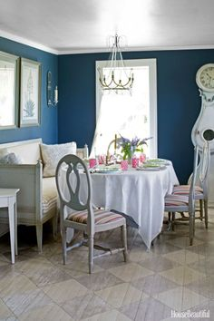 """A custom dark blue creates """"moody drama"""" in the breakfast room, used as an intimate dining spot at night. """"When the candles in the Gustavian chandelier and mirrored sconces are sparkling, it's absolutely magical,"""" Schwarz says."""