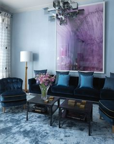 Loving the lush blue velvets paired with that striking artwork. By David Collins