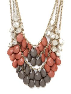 Colorblocking is made easy with this statement piece.  Acrylic organic pearls and neutral gray beads are punctuated by pops of coral.
