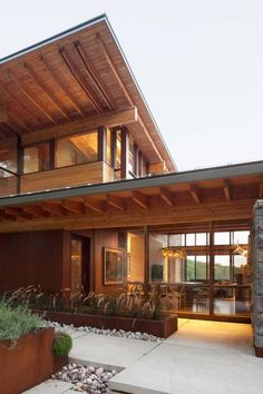 View through dining room to lake. Slick floor to ceiling glazing plays foil to the rough-hewn limestone blocks of the fin walls, which split the house into sections – kitchen/dining, living, sleeping. The colours and textures soften the building's form, hinting at nature and connecting with the landscape.  (Ben Rahn /A-Frame)