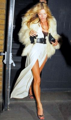 Kate Moss in a fur jacket over a white slit maxi dress, black oversized belt and black sandals