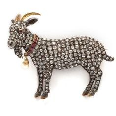 "Brooch in the form of a Toggenburg goat with a coat of pavé crown rose diamonds set in silver, chased gold horns and hooves, a three dimensional head set with a ruby eye, and a ruby collar, from which hangs a natural pearl ""bell"". Diamonds total approximately 3.6 cts. Toggenburg is a breed of goat. by nadine"