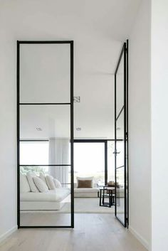 Gorgeous minimalist interior with white walls and black steel frame doors.