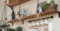 Que charmosa essa cozinha, cheia de prateleiras de madeira, taças, xícaras e colheres dependuradas, temperinhos na bancada e também dis...