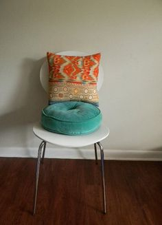 Vintage-y pillows in dramatic orange and turquoise make impact against a white backdrop.