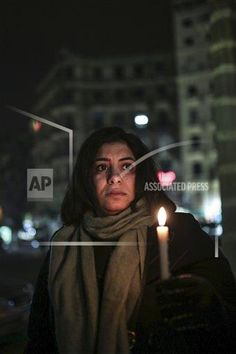 An Egyptian woman holds a candle in downtown Cairo in solidarity with the victims of Wednesday's attack on Charlie Hebdo weekly newspaper, as they join a candlelight vigil in Cairo, Egypt, Friday, Jan. 9, 2015.  French security forces ended a three-day terror rampage around Paris, killing the two al-Qaida-linked brothers who staged a murderous rampage at the satirical newspaper as well as an associate who seized a kosher supermarket to try to help them escape. (AP Photo/Mosa'ab Elshamy)