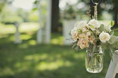 Mason jars of peach stock, lizzy, spray roses, and dusty miller lined the aisle