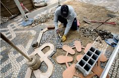 Laying a complex pattern. The craftsman, or calceteiro, uses a heavy wooden tool, a maço, to tamp the stone down into the sand bed. Pebble Floor, Pebble Mosaic, Stone Mosaic, Mosaic Art, Exterior Wall Panels, Paver Patterns, Pavement Design, Paver Designs, Small Front Gardens