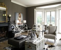 Black, white, silver, gold ...living rooms - gray taupe grasscloth wallpaper black painted fireplace gold ornate mirror white black leather Louis chair black tufted rectangular ottoman vintage trunk cowhide rug white gray striped high-back chair windows