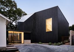 AlterStudio adds dark-stained extension to white bungalow in Texas