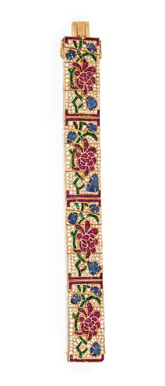 ROSE GOLD, COLORED STONE AND DIAMOND BRACELET. The articulated strap featuring four panels of floral design, each centered by flowerheads set with numerous buff-topped rubies, accented by 12 carved sapphire leaves, the meandering vines set with numerous calibré-cut emeralds, within calibré-cut ruby surrounds, length 7 inches,
