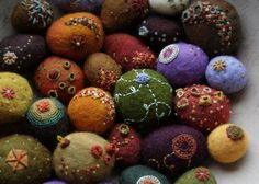 Felted stones with lots of texture.  Real stones in the middle, wool surrounding them, and stitches to add the texture.    I think of the odd little bits in nature, bumps under leaves, creeping plants, etc. when I make these.