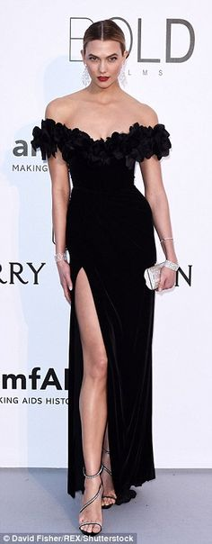 Turning heads: Karlie showed some skin in an off-the-shoulder black gown with a daringly l...