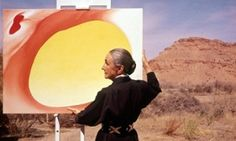 Georgia O'Keeffe adjusts a canvas from her Pelvis Series - Red With Yellow, in Albuquerque, New Mexico, in 1960.