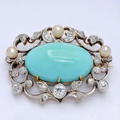 An Antique Turquoise and Diamond Brooch, circa 1900.  Centering an oval turquoise masuring 24 mm by 15 mm, surrounded by diamond-set foliate scrolls and a trio of pearls of approxiamtely 4.4 mm, mounted in platinum and 14k gold, pearls not tested for natural
