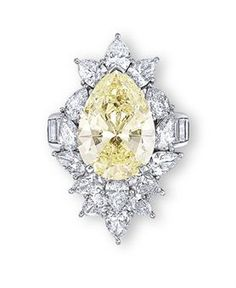 A COLOURED DIAMOND AND DIAMOND RING  Set with a pear-shaped light yellow diamond weighing 8.92 carats, within a pear-shaped diamond cluster surround, to the baguette-cut diamond quarter-hoop, mounted in platinum