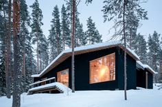 A clay-based black paint forms a protective layer across the facade of this woodland cabin in Finland, designed by Playa Architects