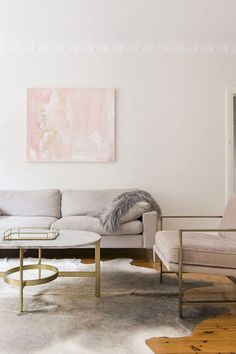 Feminine living space with wood floors, a cowhide rug, a gray sofa and blush details