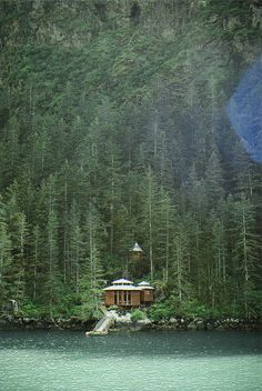 Kenai Fjords, Alaska | clear blue water + waterfront hut style home on an evergreen covered mountainside