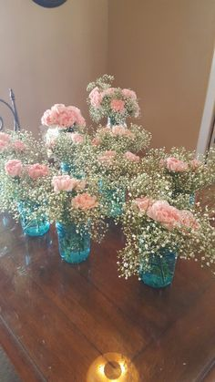 Blue mason jars with pink carnations and babys breath for gender reveal