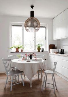 столовая в скандинавском стиле, белый круглый обеденный стол, деревянные стулья, деревянная люстра