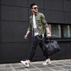 Look masculino com jaqueta militar, camiseta longtail e tênis adidas