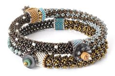 This set of two bracelets slide on and off without a clasp. The bracelets are beaded over a rubber core. Focal beads are fastened to peyote