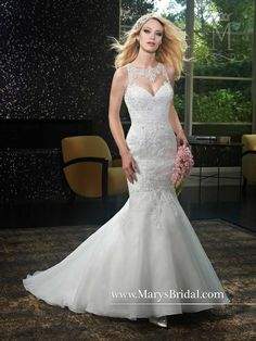 Organza bridal gown with fit and flare silhouette, scoop neck, no sleeves, sheer back, lace applique, beaded embellishment, back zipper and buttons, and chapel train.