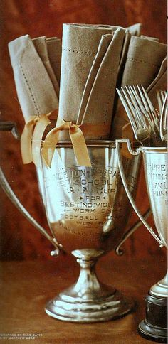 Napkin wrapped silverware in silver trophies, I love this. Pretty for a buffet