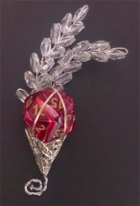 This is the up close picture of the boutonniere. I used the Chessex Scarab Scarlet with gold numbers. All the dice I used to make the boutonnieres for my husband,the best man, and the groomsmen (and a set of dice for myself), I got at GenCon last year. Also, the die can come out and be used.