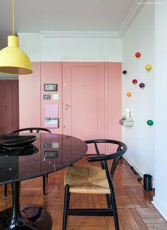 Sala de jantar tem parede pintada de rosa, mesa saarinen preta e cadeira wishbone.