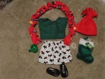 Evergreen cotton top with velcro closure in the back. Cotton skirt with scottie dogs and holly leaves has an elastic waist. Red fleece hat and multicolor scarf. Clothing is exclusive to For The Hope Chest. Black ballerina flats by Sophia's with embroidered flowers. Green stocking. includes Green hot chocolate mug made out of acrylic and a beaded bracelet. 1 available