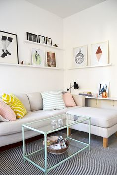 Elina Dahl / Living - white - rug - pattern - art wall - shelves - pillows - pale, pink, yellow - glass