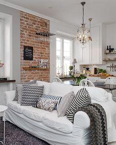 Un salon et une salle à manger ouverts sur la cuisine. Ici, le côté brut de la brique s'oppose à l'éclat du blanc tout autour. (Alvhemmakleri)