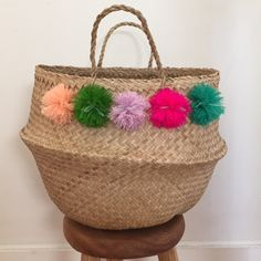 """handmade basket with colorful pompoms as shownapproximately 14"""" tall not including handleas seen in Real Simple magazine please allow approximately four weeks for deliveryall sales final"""