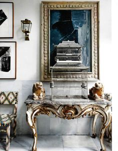 birdcage in the entryway. love that chunky frame.