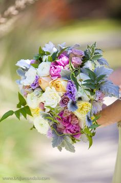 Gardenias, peonies, roses, carnations, and ranunculus blooms are paired with dusty miller leaves for a beautiful bouquet.