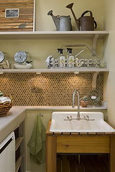Honeycomb backsplash. Laundry detergent in a penny candy jar, succulent in the corner and Watkins Lemon All Purpose Cleaner on the shelf. Now this room is a thing of beauty.  Love it all.