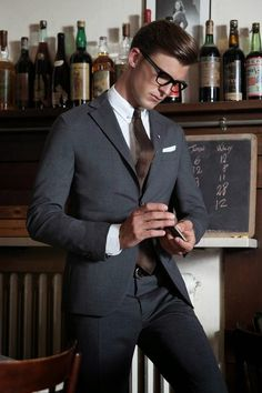 Men's dark gray suit with white shirt and brown tie