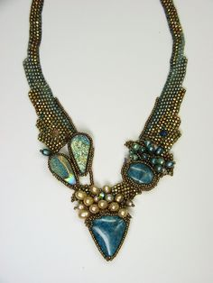 Neckpiece by the always-original Amolia Willowsong. Blue apatite and golden-blue coated drusy cabochons and pearl cluster on a simple freeform peyote stitch neckband. Many more nice similar pieces on her website.