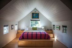 A bedroom with a cathedral ceilings. It has wood floors and tree side windows that make it warm and inviting.